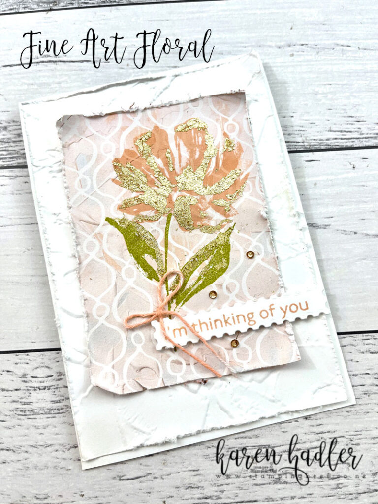 Fine art Floral. A card on a white base a textured mat of white. On top of that is a pink and white Design er Series paper that has its edges roughed. On top of the DSP is a pink Bloom with gold highlights and there is a green stem and leaves also with gold highlights.. The sentiment is I'm Thinking of you in a rectangle stamp like piece of white card stock. there is a small pink bow above the sentiment.