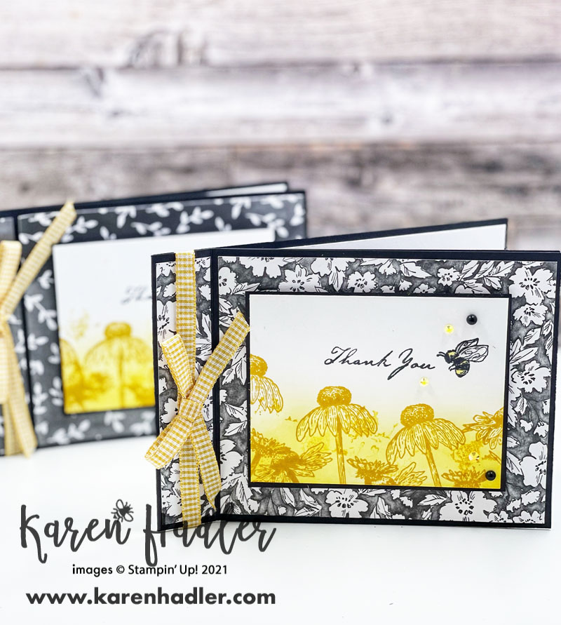 Thank - you Card with nature's Harvest. Quick and easy with the simple book fold style. The Card base is black with black and white flowery Designer Series Papers. The feature is a white rectangle with a yellow blended background on the bottom half with darker yellow daises. The words say Thank you and there is a Bee next to them. There is also some gorgeous yellow gingham ribbon down the left hand side.