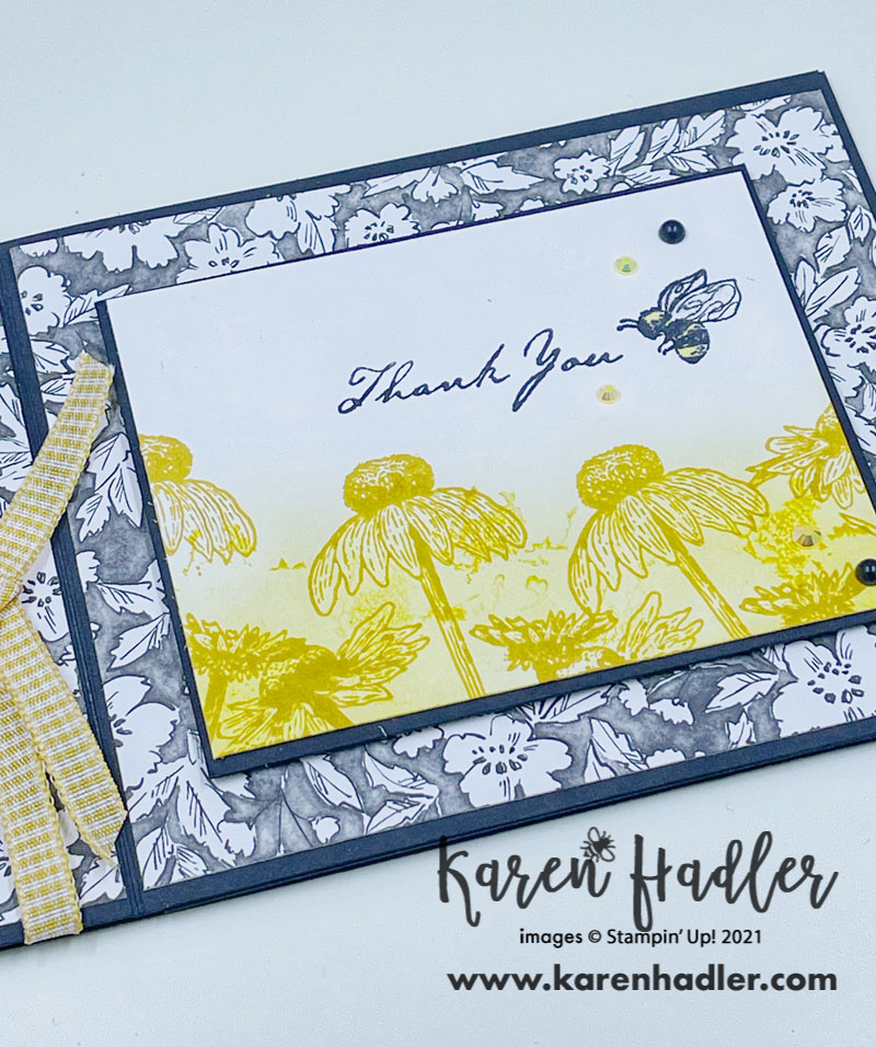 A closer look atThank - you Card with nature's Harvest. Quick and easy with the simple book fold style. The Card base is black with black and white flowery Designer Series Papers. The feature is a white rectangle with a yellow blended background on the bottom half with darker yellow daises. The words say Thank you and there is a Bee next to them. There is also some gorgeous yellow gingham ribbon down the left hand side.
