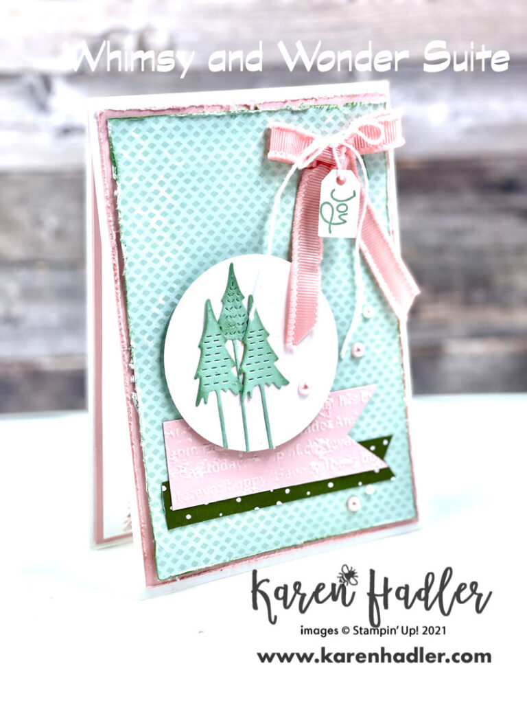 The Joy of Whimsy and Wonder. This stunning card has a beautiful colour palette of Mint macaroon and Blushing Bride. Ther'e 3 trees on a pink blended circle sitting on top of  a pink embossed strip and a green tagged strip. there is a large pink bow top right hand corner with white twine tied in a bow with a tag that says Joy.