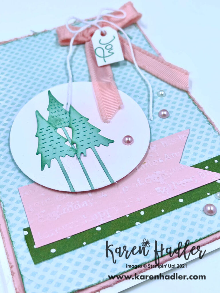 A close up ofThe Joy of Whimsy and Wonder. This stunning card has a beautiful colour palette of Mint macaroon and Blushing Bride. Ther'e 3 trees on a pink blended circle sitting on top of  a pink embossed strip and a green tagged strip. there is a large pink bow top right hand corner with white twine tied in a bow with a tag that says