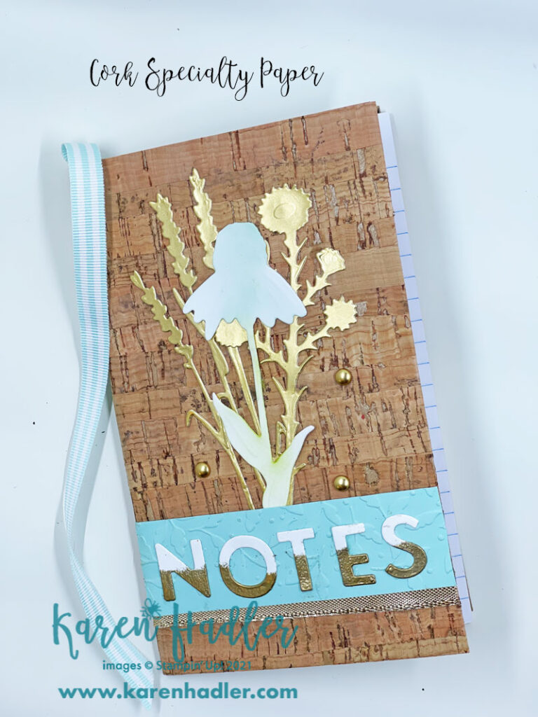 Cork Specialty paper this picture show a note book covered by what looks like cork. There are gold foil stems and a white daisy sponged in blue and green. Across the bootom is a strip of pool pard embossed card with the letters notes. These letters are half white and half gold. There is also a striped blue party ribbon along the spine to be used as a book mark.
