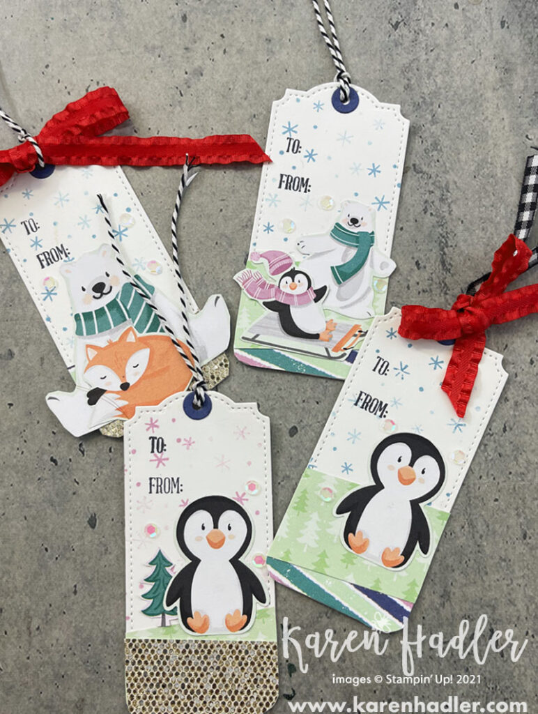 penguin Playmates tags. Photo showing four Christmas tags each background has small snowflakes and the words to and from. Two have just the penguin and two have polar bears and foxes. They are tied at the top with black and white twine and red ribbon.