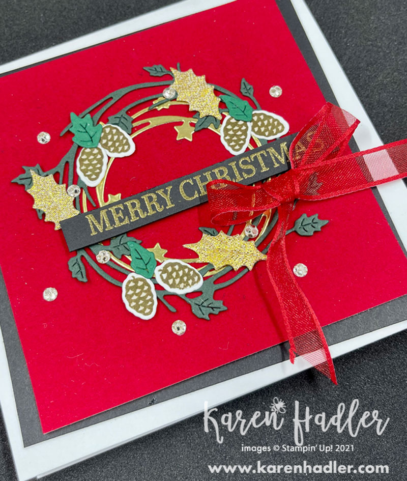 Sparkle of The season card. Close up with The picture shows a card on a white base with a black mat and a red velvet top mat, which looks very lush. The wreath is built on top of this. It consists of a dark green circle with leaves and a gold circle with stars. On top of this is pine cones, lighter green leaves and some gold leaf embellishments. The large lettered Merry Christmas is Gold embossed on a black strip and runs across the middle with a sheer bow tied underneath.