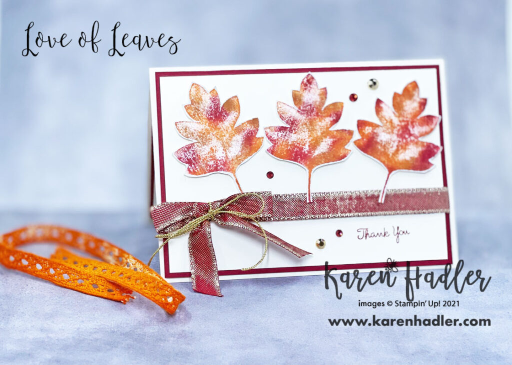 Love of leaves. A picture of a very vanilla card base and Cherry cobble matting. The card is in landscape mode with a very vanilla mat on top. The 3 large autumn coloured leaves run across the top. A red ribbon with gold threads runs across the middle with a bow. The sentiment bottom right is thank you.