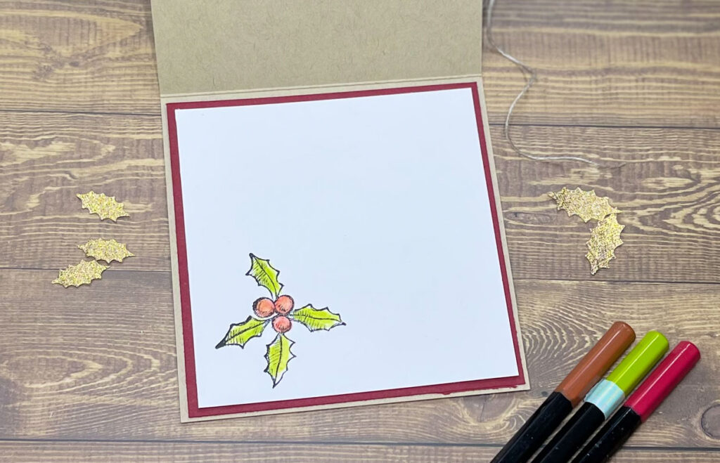 Happy Holly-Days and Water Colour pencils. This is the inside of the card with a holly leaves and berries in the bottom left hand corner. The leaves are green and the berries are red.