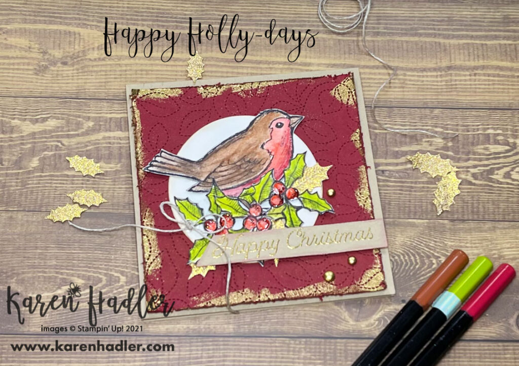 Happy Holly-Days wth Water Colour Pencils . A square card on a Crumb Cake base. The mat is in Cheery Cobble (red) and patterned with leaves. There is gold embossing around the edges. The bird is on a circle that has been sponged with Balmy Blue.  It has been coloured brown and red with 3 holly berries and leaves beneath it. Merry Christmas is Gold embossed on Crumb cake card stock and is in the form of a tag across the bottom of the card. There is a small linen bow to the left of this and 3 gold embellishments.