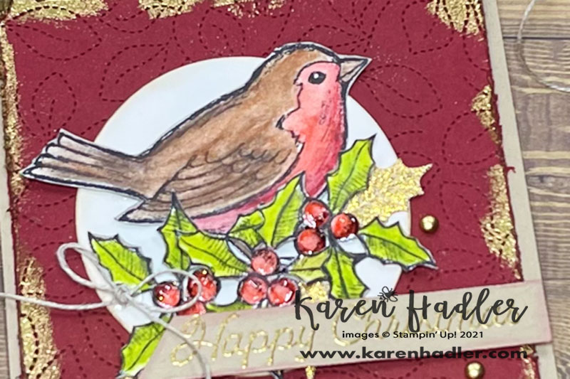 A close up of theHappy Holly-Days wth Water Colour Pencils . A square card on a Crumb Cake base. The mat is in Cheery Cobble (red) and patterned with leaves. There is gold embossing around the edges. The bird is on a circle that has been sponged with Balmy Blue.  It has been coloured brown and red with 3 holly berries and leaves beneath it. Merry Christmas is Gold embossed on Crumb cake card stock and is in the form of a tag across the bottom of the card. There is a small linen bow to the left of this and 3 gold embellishments.