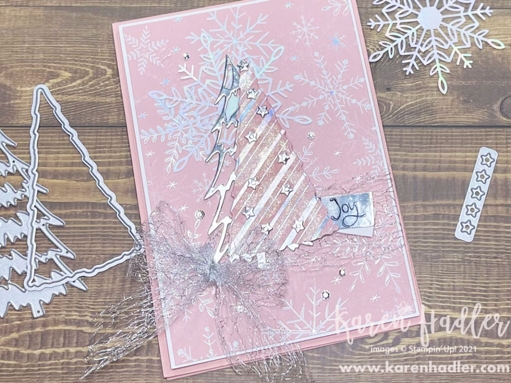 Whimsy and Wonder a picture on a pink card base with gorgeous Pink Designer series Paper that has white snowflakes. The feature is a Pink and Silver Tree with a large silver mesh bow to the left of it. There is a Silver foil tag that says Joy.