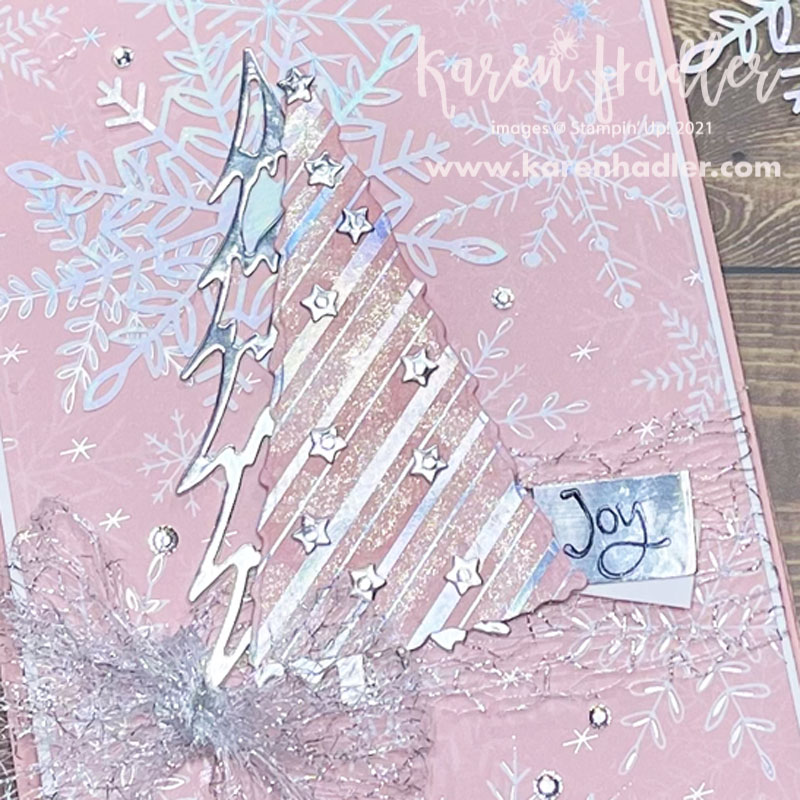 A close up of the tree with Whimsy and Wonder  on a pink card base with gorgeous Pink Designer series Paper that has white snowflakes. The feature is a Pink and Silver Tree with a large silver mesh bow to the left of it. There is a Silver foil tag that says Joy.