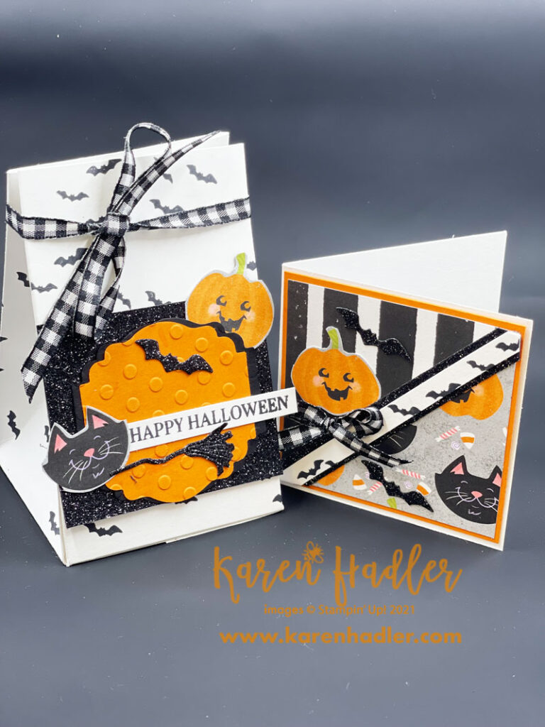 Cute Halloween picture of a gift bag and gift card > The bag is white with black bats stamped on it and tied at the top with black and white Gingham Ribbon. On the front is a square of Black glitter paper and on top of that is a pumpkin pie (orange) semi circle shaped piece of card. Tucked under top right and is a small pumpkin character and bottom left and balck smiling cat. there is also a black glitter witches broom and bat. The words read Happy Halloween. The gift card co-ordinates with the gift bag. there is a white strip with black bats stamped on it running from bottom left to top right corner. Top left of card is black and white stripes with a pumpkin character and black glitter bat. There is also a small black and white Gingham bow tied under the pumpkin. Bottom right s the cute Halloween DSP with a cat, pumpkin, bat and lollies.
