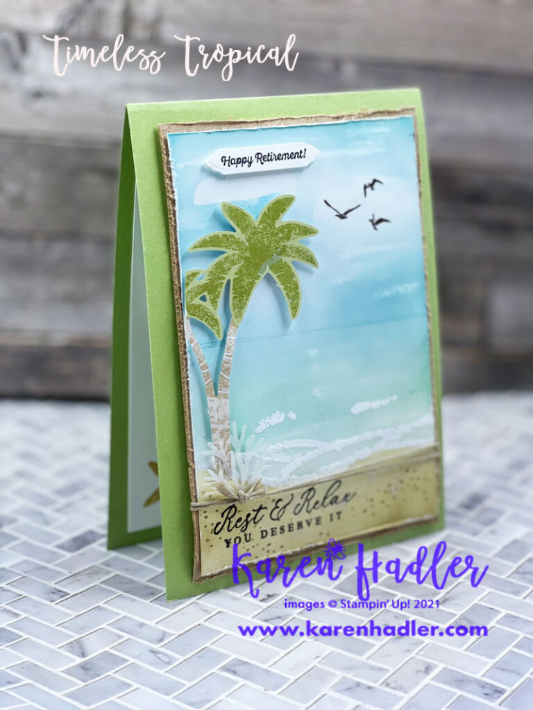 Timeless Tropical Retirement card. A water coloured card showing the ocean with white waves a blue sky and Sahara Sand To the left is a palm tree and at the top it says Happy Retirement. At the bottom Rest and relax is stamped.