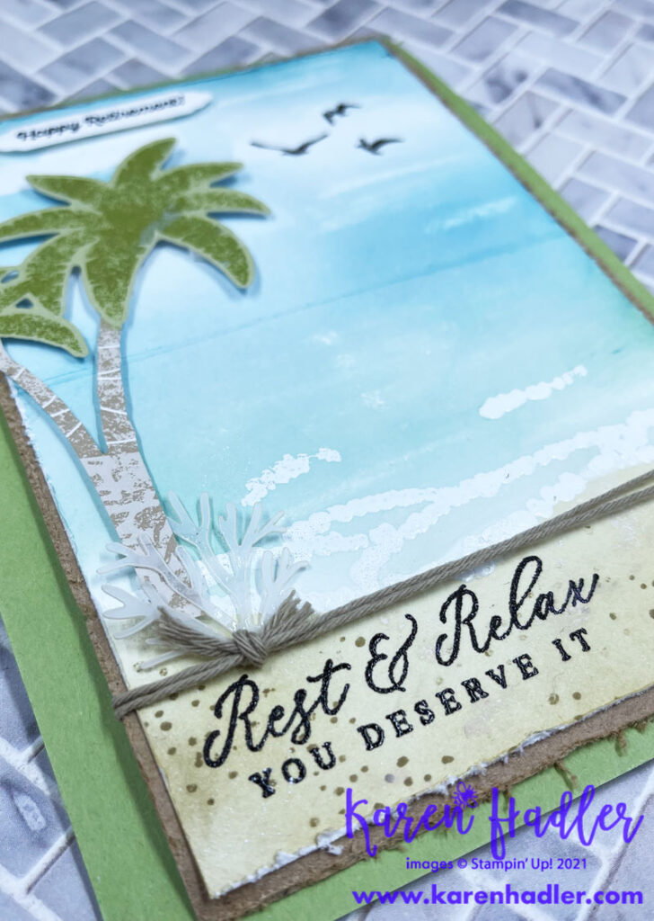A closer look atTimeless Tropical Retirement card. A water coloured card showing the ocean with white waves a blue sky and Sahara Sand To the left is a palm tree and at the top it says Happy Retirement. At the bottom Rest and relax is stamped.