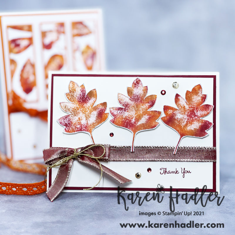 A close up ofLove of leaves. A picture of a very vanilla card base and Cherry cobble matting. The card is in landscape mode with a very vanilla mat on top. The 3 large autumn coloured leaves run across the top. A red ribbon with gold threads runs across the middle with a bow. The sentiment bottom right is thank you.